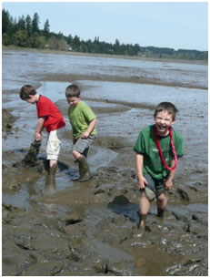 children playing in beach mud